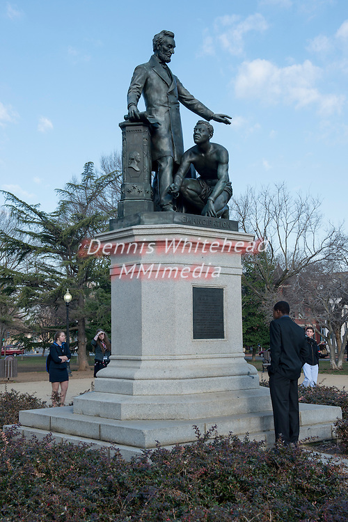 A high school student reads the inscription on the statue commemorating the Emancipation Proclamation in Washington, DC's Lincoln Park.
