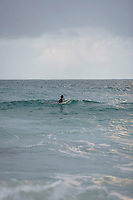 Surfer sitting on surfboard in sea side view
