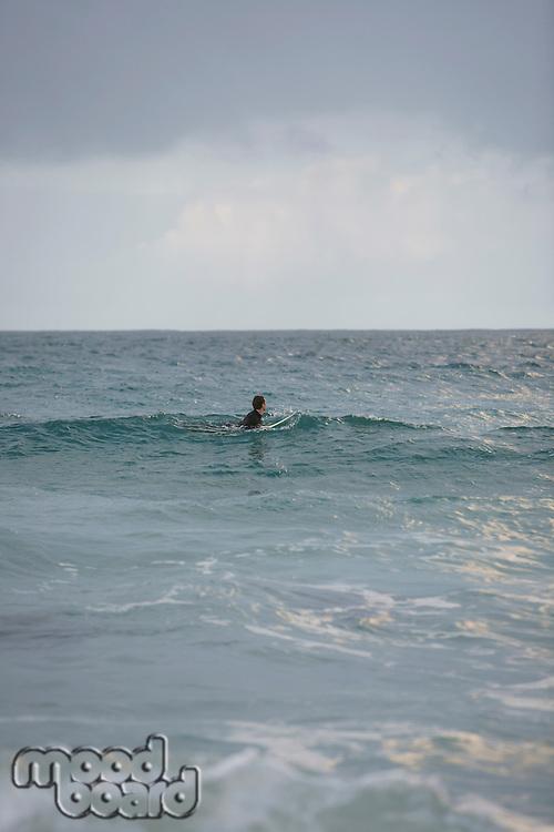 Surfer sitting on surfboard in sea side view