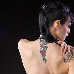 A young, tattooed woman, looking over her shoulder.