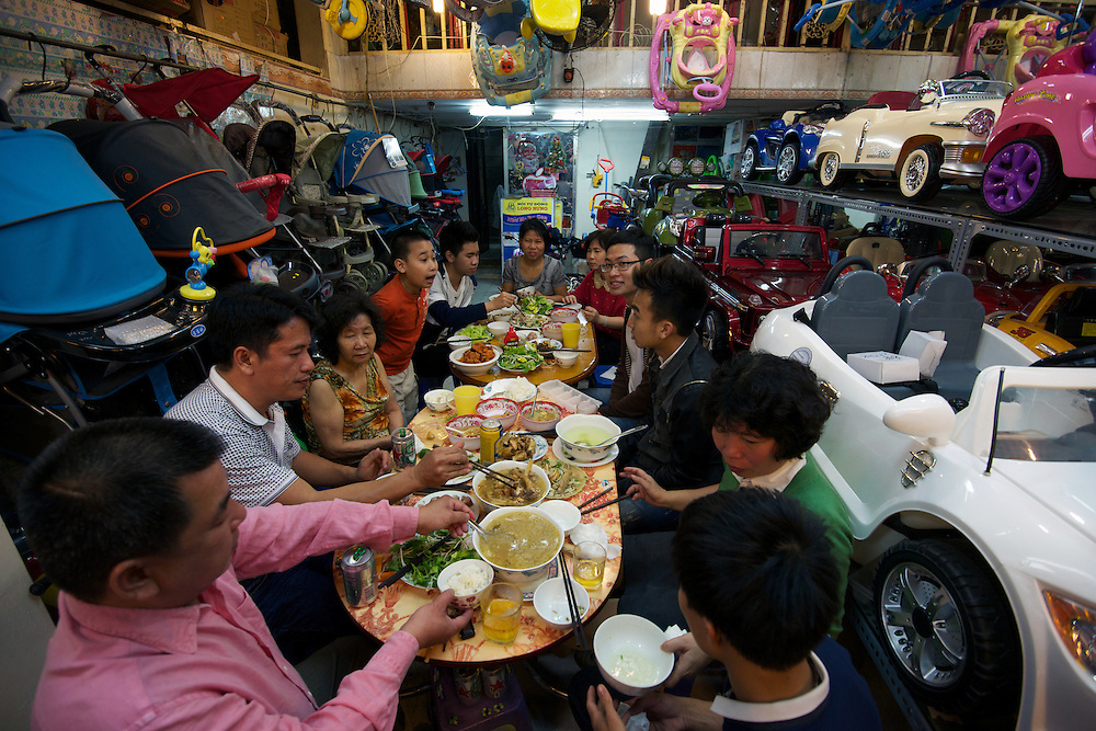 "A family celebrate ""Tet"" (New Year) with a feast inside their shophouse business of selling prams and children's cars, Old Quarter."