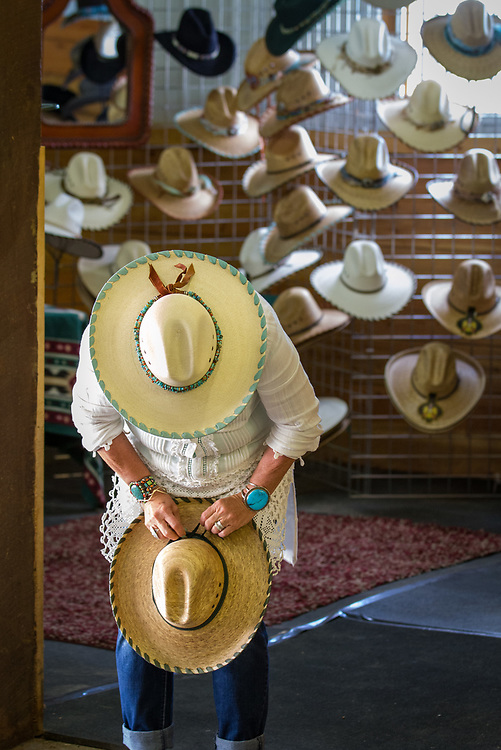 A hat vendor straightens her wares at the Custer County Cowboy Gathering and Chuckwagon Cook Off.