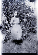 fashionable dressed young adult woman in garden rural USA 1920s 1930s