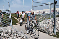 A group of men, all migrant workers, travel on bicycles between a path between large box retail stores in Leamington. Bikes are a popular form of transportation for the workers and the big box stores are a popular weekend destination.
