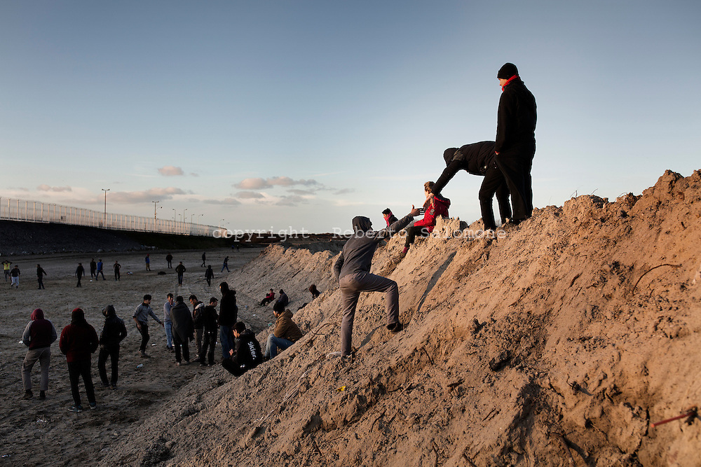 FRANCE, Calais - Refugees are seen outside the &quot;Jungle&quot; refugee camp in the outskirts of the city of Calais in northern France on January 28, 2016. Refugees and migrants spend months and months in the camp. Police forces created a sand barrier between the camp and the highway in order to control the refugees who try to get over the barriers that try to get inside trucks that leave for the United Kingdom.<br /> Ph. Roberto Salomone