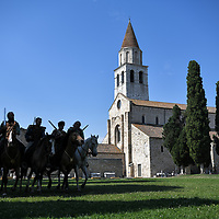Aquileia, Italy - 17 June 2018: Celtic knights in silhouette ride their horses in front of the Basilica Santa Maria Assunta at Tempora in Aquileia, ancient Roman historical re-enactment