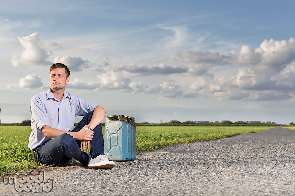 Full length of young man with empty gas can sitting by country road