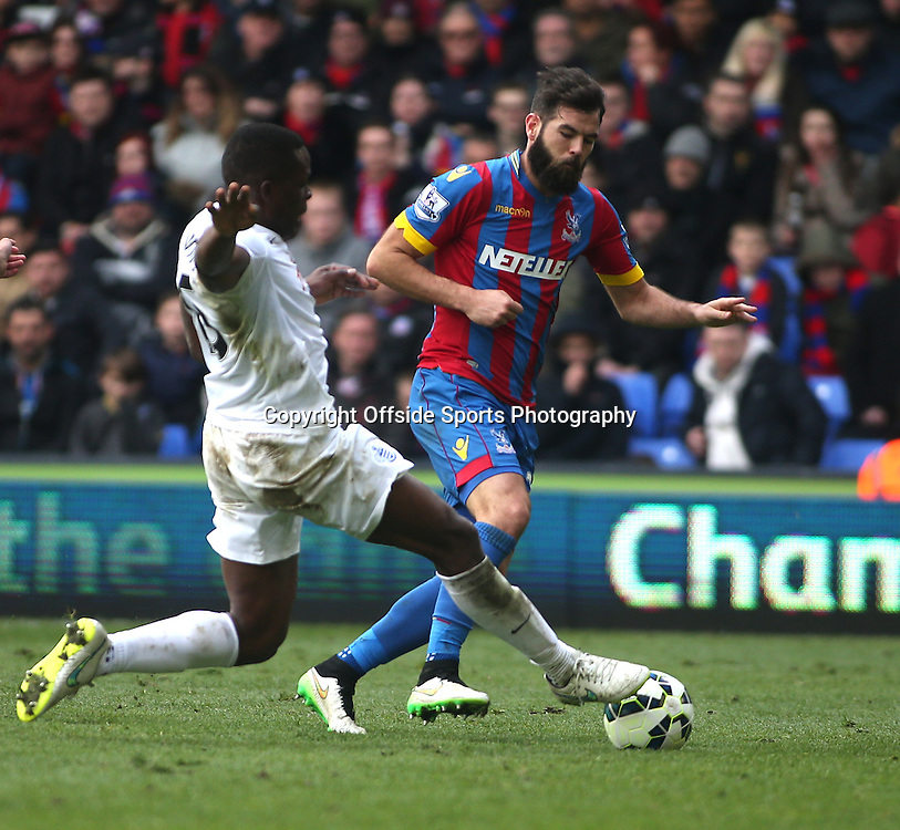 14 March 2015 - Barclays Premier League - Crystal Palace v Queens Park Rangers - Nedum Onuoha of QPR slides in on Joe Ledley of Palace.<br /> Photo: Ryan Smyth/Offside