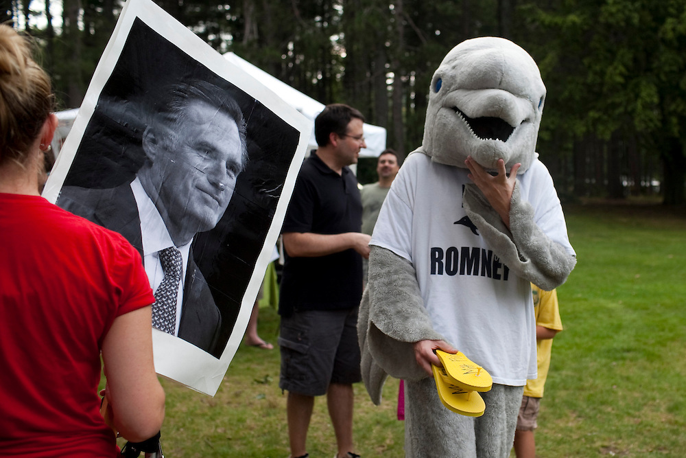 """Concord, N.H. -- A detractor of former Mass. governor and 2012 presidential candidate Mitt Romney dressed as """"Flip Romney"""" to express his disapproval turns to look at a Romney supporter at a Tea Party Express rally at Rollins Park in Concord, N.H. on Sept. 4, 2011."""