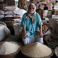 A rice seller sits among his varieties of rice for sale in the municipal market in Srimongol in the tea growing region of north east Bangladesh