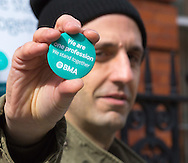 A protester displays a badge with its BMA message of solidarity as striking junior doctors picket outside Great Ormond Street Hospital for Children, Bloomsbury, London.<br /> Picture by Paul Davey/Focus Images Ltd +447966 016296<br /> 26/04/2016