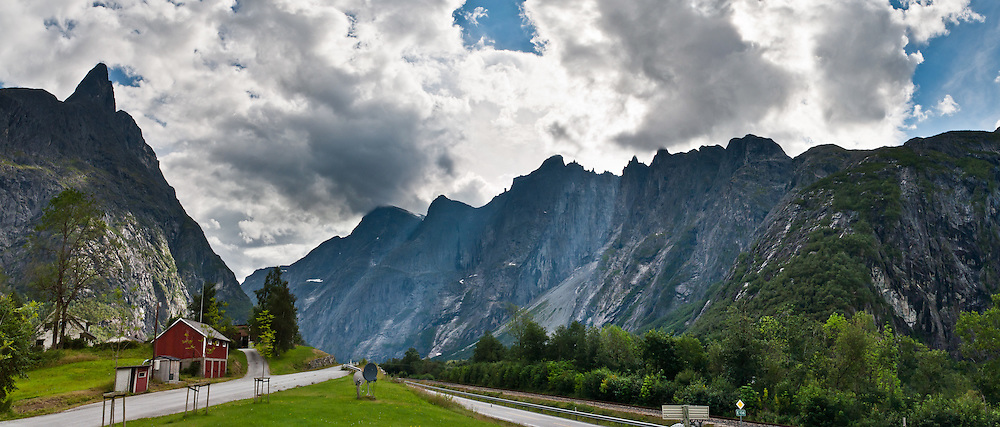 The Troll Wall is the tallest vertical rock face in Europe, about 1100 meters (3600 feet) from base to summit. Located within Reinheimen National Park, the Troll Wall (Trollveggen) and Trolltindane (Troll Peaks) soar high above the Romsdalen valley near Åndalsnes, Norway. The gneiss rock summit ridge overhangs its base by nearly 50 meters (160 ft). Parachute BASE jumping from Troll Wall has been illegal since 1986, but climbing the face is allowed, as is hiking up the gentler back. Trollveggen is in Rauma municipality, Møre og Romsdal county. Panorama stitched from 3 overlapping photos.