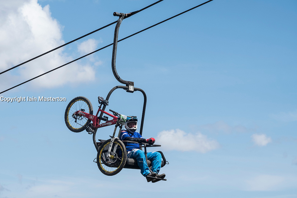 Downhill mountain bike cyclist on chairlift at Glen Coe on way to competition in Scotland, united Kingdom