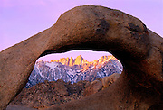 0671-1002 ~ Copyright: George H.H. Huey ~ Mt. Whitney and the Sierra Nevada Mountains, seen through a natural arch in the Alabama Hills at sunrise.  Eastern Sierra nevada, California.