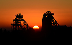 © Licensed to London News Pictures. 01/10/2015. Doncaster, UK. The sun sets behind the pit head winding gear at Hatfield Colliery, Doncaster, South Yorkshire. Hatfield Colliery was one of the last deep seam coal mines in the UK and was closed this summer after nearly 100 years of production. Photo credit : Anna Gowthorpe/LNP