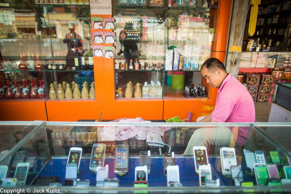13 MARCH 2013 - ALONG HIGHWAY 13, LAOS: A Chinese cell phone vendor waits for a customer in the Chinese market near the end of Highway 13 in the Boten Special Economic Zone. The SEZ is in Laos immediately south of the Lao Chinese border. It has turned into a Chinese enclave but many of the businesses struggle because their goods are too expensive for local Lao to purchase. Some of the hotels and casinos in the area have been forced to close by the Chinese government after reports of rigged games. The paving of Highway 13 from Vientiane to near the Chinese border has changed the way of life in rural Laos. Villagers near Luang Prabang used to have to take unreliable boats that took three hours round trip to get from the homes to the tourist center of Luang Prabang, now they take a 40 minute round trip bus ride. North of Luang Prabang, paving the highway has been an opportunity for China to use Laos as a transshipping point. Chinese merchandise now goes through Laos to Thailand where it's put on Thai trains and taken to the deep water port east of Bangkok. The Chinese have also expanded their economic empire into Laos. Chinese hotels and businesses are common in northern Laos and in some cities, like Oudomxay, are now up to 40% percent. As the roads are paved, more people move away from their traditional homes in the mountains of Laos and crowd the side of the road living off tourists' and truck drivers.    PHOTO BY JACK KURTZ