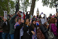 A crowd of onlookers in Parliament Square, London, cheering at 11am as Catherine Middleton's car passes on the way to Westminster Abbey for he marriage to Prince William. The wedding was held at Westminster Abbey. Tens of thousands of people lined the streets to wish the couple well before and after the ceremony.