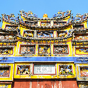 Ornate decorations on top of a courtyard gate at the Imperial City in Hue, Vietnam. A self-enclosed and fortified palace, the complex includes the Purple Forbidden City, which was the inner sanctum of the imperial household, as well as temples, courtyards, gardens, and other buildings. Much of the Imperial City was damaged or destroyed during the Vietnam War. It is now designated as a UNESCO World Heritage site.