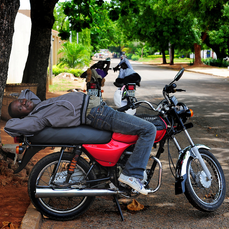 12-05-29   - LOME, TOGO -    Zemidjan ('take me quickly' in  Fon) driver Eric Pidjolo demonstrates how he sleeps on his motorcycle in Lomé, Togo on May 29. Underpaid, rarely thanked and working all hours to make a meagre living, they find very few moments of calm and quiet in their lives. And so, the moto-taxi men have perfected various ways of calmly sleeping on their motorbike as they wait for  their next customer. And so, on the move amidst the chaos and bustle of daily life, they relax and sleep.  Photo by Daniel Hayduk