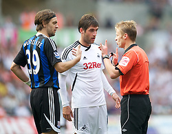 SWANSEA, WALES - Sunday, October 2, 2011: Swansea City's Danny Graham and Stoke City's Jonathan Woodgate are spoken to by referee Mike Jones during the Premiership match at the Liberty Stadium. (Pic by David Rawcliffe/Propaganda)