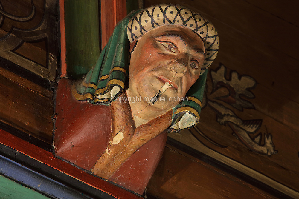 Carved and painted roof bracket with head of a serious looking man wearing a headdress, architectural detail of the painted wooden ceiling in the shape of a boat's hull, in the Salle des Povres or Room of the Poor, almost 50m long, in Les Hospices de Beaune, or Hotel-Dieu de Beaune, a charitable almshouse and hospital for the poor, built 1443-57 by Flemish architect Jacques Wiscrer, and founded by Nicolas Rolin, chancellor of Burgundy, and his wife Guigone de Salins, in Beaune, Cote d'Or, Burgundy, France. The hospital was run by the nuns of the order of Les Soeurs Hospitalieres de Beaune, and remained a hospital until the 1970s. The building now houses the Musee de l'Histoire de la Medecine, or Museum of the History of Medicine, and is listed as a historic monument. Picture by Manuel Cohen