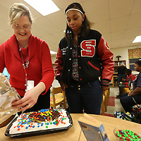 "Adam Robison | BUY AT PHOTOS.DJOURNAL.COM<br /> Jennifer King, Shannon High School librarian, stands with Raven Childs, a Senior, uncovers her cake for the edible books festival at Shannon High School Tuesday night. Her display was based on the book "" A Solitary Blue"" by Cynthia Voigt."