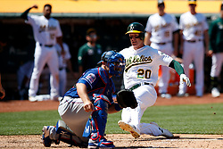 OAKLAND, CA - JULY 28:  Mark Canha #20 of the Oakland Athletics slides into home plate to score a run past Tim Federowicz #50 of the Texas Rangers during the sixth inning at the RingCentral Coliseum on July 28, 2019 in Oakland, California. The Oakland Athletics defeated the Texas Rangers 6-5. (Photo by Jason O. Watson/Getty Images) *** Local Caption *** Mark Canha; Tim Federowicz