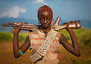 Bana young woman carrying Kalashnikov rifle on her shoulders. Omo valley, Ethiopia.<br />