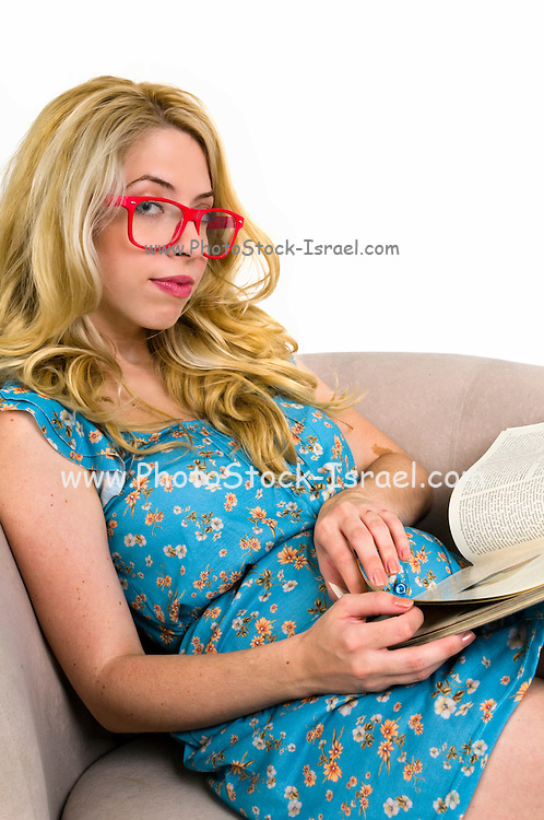 Young blond woman reads a magazine