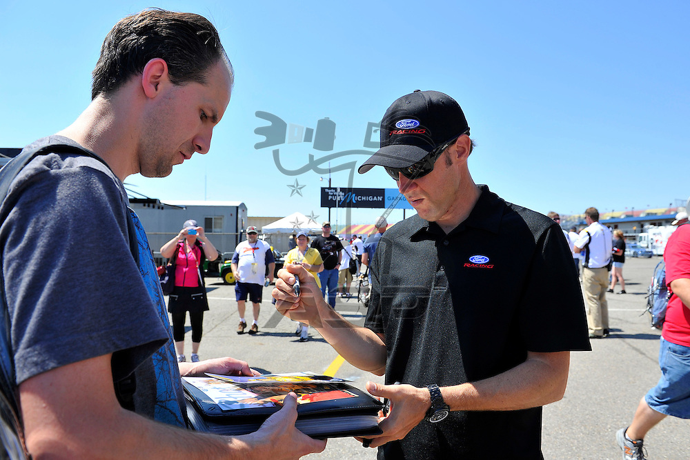 Brooklyn, MI - JUN 15, 2012: Matt Kenseth (17) signs autographs in the garage during practice for the Quicken Loans 400 race at the Michigan International Speedway in Brooklyn, MI.