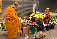 Buddhist monk giving blessings after receiving alms, Ton Payom Market, Chiang Mai, Northern Thailand