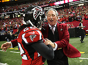 Atlanta Falcons owner Arthur Blank congratulates cornerback Asante Samuel after a win against the Seattle Seahawks in the 2013 NFL Playoffs.