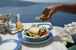 man pouring olive oil on a greek salad in Greece
