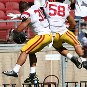 USC Fullback and Special Teams star, Soma Vainuku (#31) jumps high to celebrate with J.R. Tavai (#58) after USC prevailed over Stanford 13-10 at Stanford Stadium, Palo Alto, California.   Photo by Barry Markowitz, 12:30pm, 9/06/14
