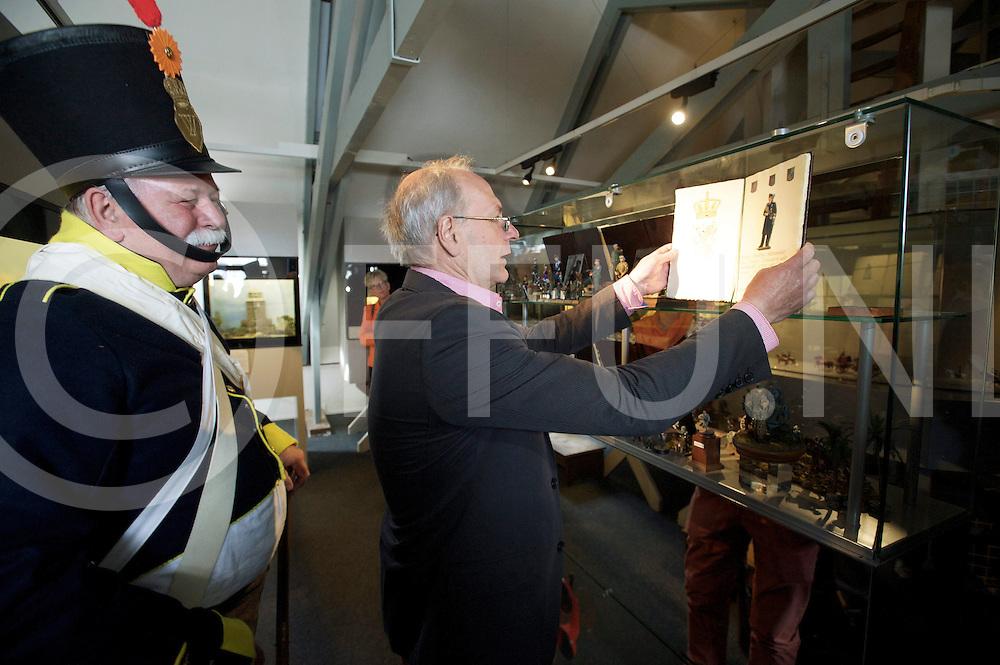 OMMEN - Willem Alexander bij zetten in Tinnen Figuren museum..Foto: OV voorzitter Jan Steen plaatst het boekje met het finguurtje in de vitrine..FFU PRESS AGENCY COPYRIGHT FRANK UIJLENBROEK.