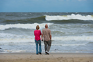 Spring Lake, NJ US -- Sept 3, 2016. A couple stands on the beach watching the ocean churn before an impending storm .