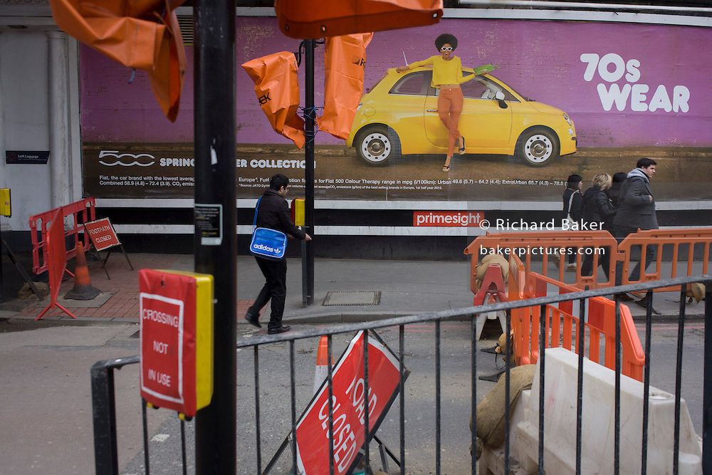 Pedestrians walk beneath a wide billboard advertising the Fiat 500 with a 70s fashion theme.