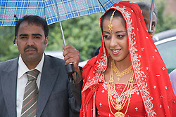 Bride in traditional Asian dress and her uncle arriving for her wedding,