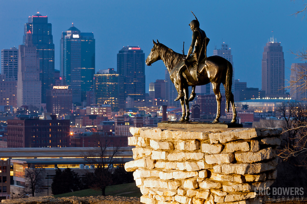 Scout Statue in Penn Valley Park overlooking downtown Kansas City, Missouri skyline at dusk.