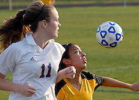 A Lake Braddock soccer player keeps her eye on the ball while being defended by a Chantilly player.