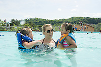 Megan Gibson and her daughters get cooled off in the pool following the 70th Anniversary celebration of the Kiwanis Pool in St. Johnsbury Vermont.  Karen Bobotas / for Kiwanis International