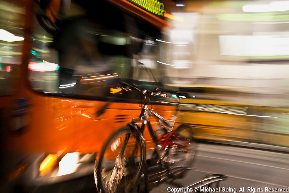 Motion blur pan shot of orange public bus with a bicycle rack and bicycle. Shot on Hollywood Blvd, Hollywood, CA USA