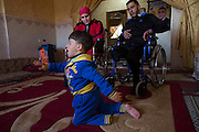 Wounded Wael al-Namlah, 26, and his wife Asraah as  their three year-old son Sharif  crawls on the carpet at their home in Rafa,Gaza January 20,2015. Wael lost one of his legs, his wife lost both and their son lost one leg during last summer's war between Israel and the Hamas-controlled Gaza Strip. The incident happened on one of the darkest days during the war that has been named 'Black Friday'. Palestinians claim 130-150 were killed in the Rafa area of southern Gaza during a breakdown of a ceasefire agreement during a tunnel incident between Hamas and Israeli troops .<br />