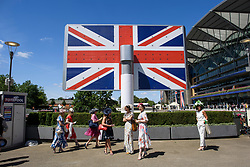 © Licensed to London News Pictures. 21/06/2018. London, UK. Racegoers stand underneath the Union Flag Ladies Day at Royal Ascot at Ascot racecourse in Berkshire, on June 21, 2018. The 5 day showcase event, which is one of the highlights of the racing calendar, has been held at the famous Berkshire course since 1711 and tradition is a hallmark of the meeting. Top hats and tails remain compulsory in parts of the course. Photo credit: Ben Cawthra/LNP