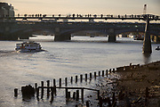 "A pleasure boat passes old riverside wharf timbers and the bank of the river Thames, before continuing under pedestrians on the Millennium Bridge, on 30th October 2017, at Queenhithe in the City of London, England. Queenhithe is also the name of the ancient, but now disused, dock which derives from the ""Queen's Dock"", or ""Queen's Quay"", which was probably a Roman dock (or small harbour). The dock existed during the period when the Wessex king, Alfred the Great, re-established the City of London, circa 886 AD."