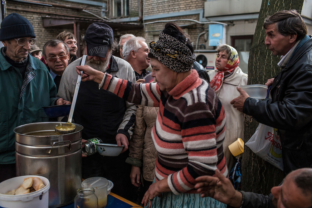 Hot soup is served to people in need of a free meal on Thursday, October 16, 2014 in Donetsk, Ukraine. Many older residents have not received pension payments in months and no longer have enough money to buy food.