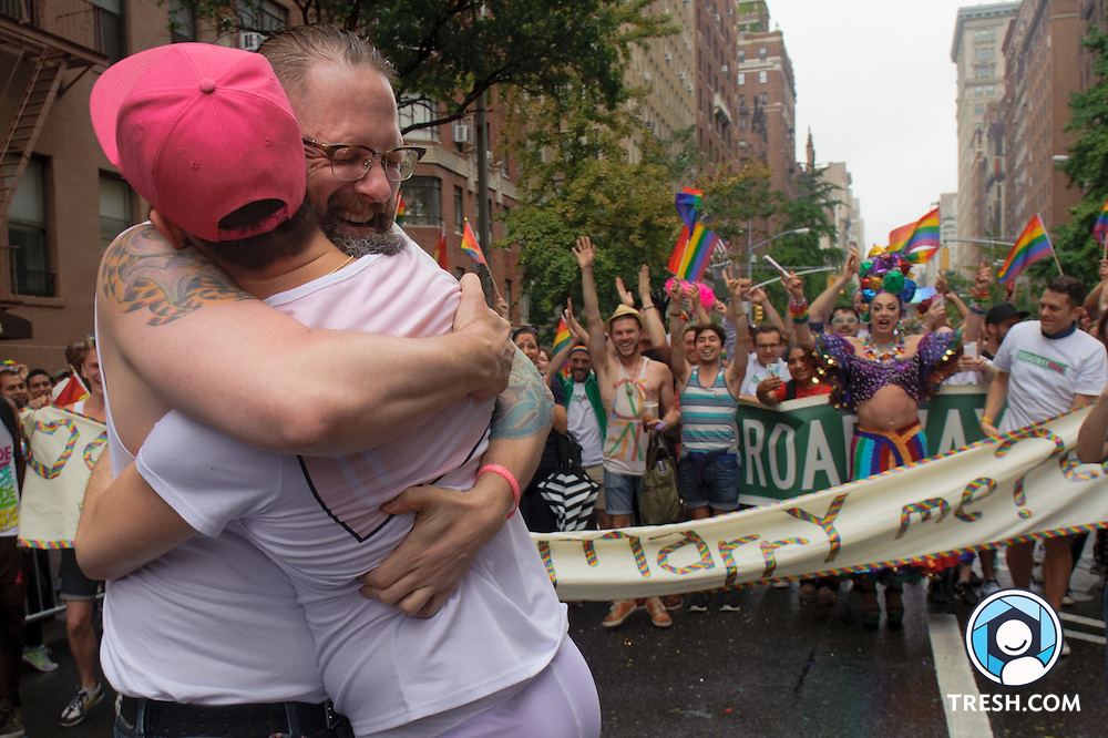 "Erik Sudduth, facing the camera, surprised Sam Branman during NYC Pride 2015 by proposing to get married. The couple have been together two-and-a-half years. ""I told my coworkers Friday,"" Sudduth said, ""if the Supreme Court handed down the decision that I wasn't going to wait."" Branman said yes. Marchers with Broadway Impact helped by unfurling a banner that read, ""Will you marry me?"""