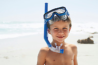 Portrait of cute little boy wearing snorkel while standing on beach