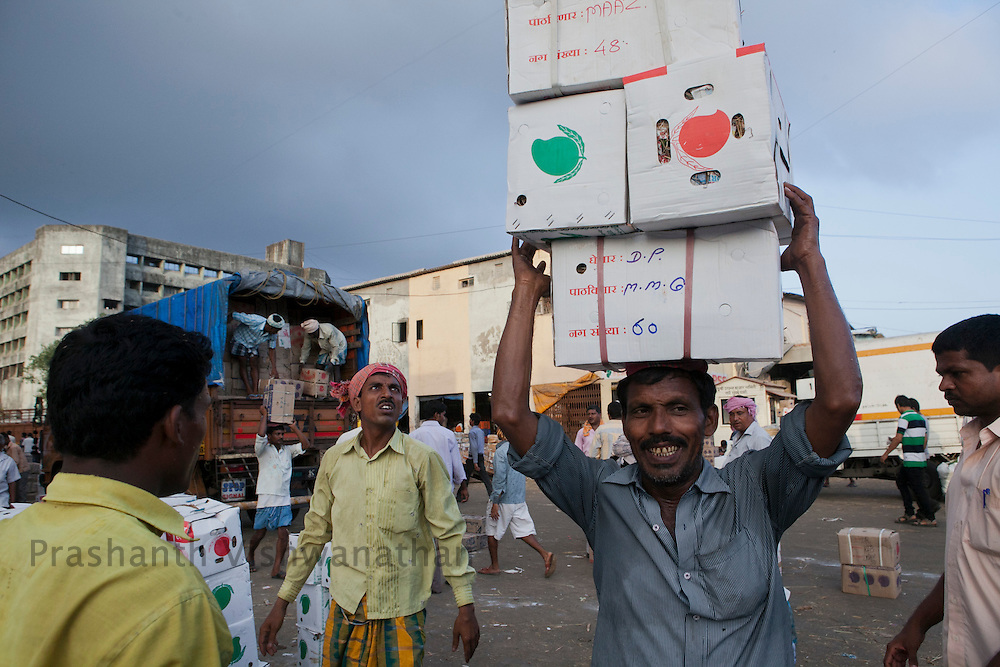 Daily wage laborers off load boxes of mangoes arriving from farms at the Vashi wholesale market, in Greater Mumbai, India, on Tuesday May 22, 2012. Photographer: Prashanth Vishwanathan/NYT