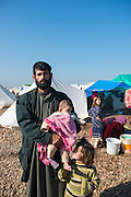 This is Ragheb Ramadan, age 27 and from the Syrian town of Talhiyeh, standing with his three children in a camp for internally displaced persons. During our conversation about the situation in Syria, Ragheb told me that he fights for Jabhat al Nusra and comes to the camp only occasionally to see his family.<br />